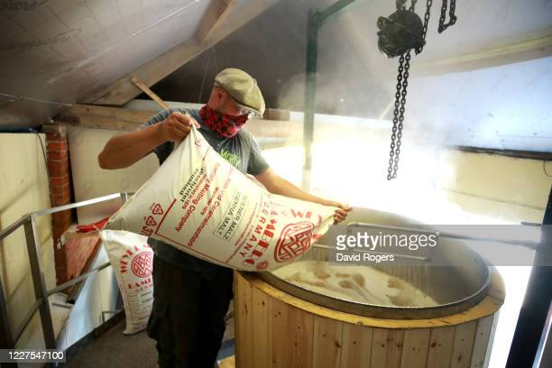 Tanel Karjus, the master brewer, pours the grain into the mash tun where it is mixed with hot water at Silverstone Brewery on May 28, 2020 in...