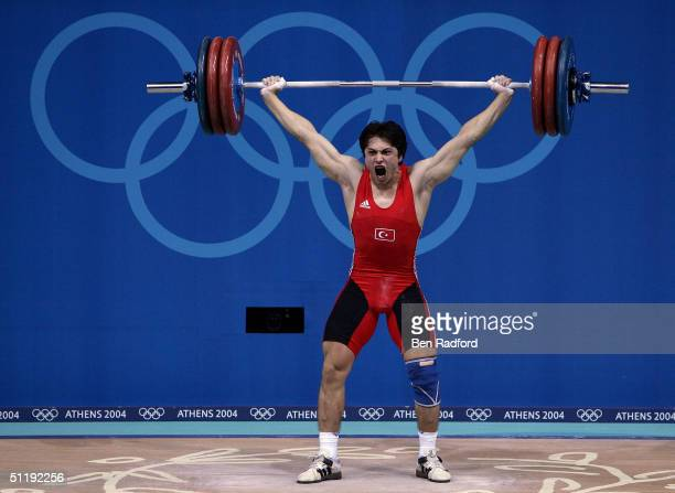Taner Sagir of Turkey makes his Olympic record setting lift in the snatch portion of the men's 77 kg category weightlifting competition on August 19...