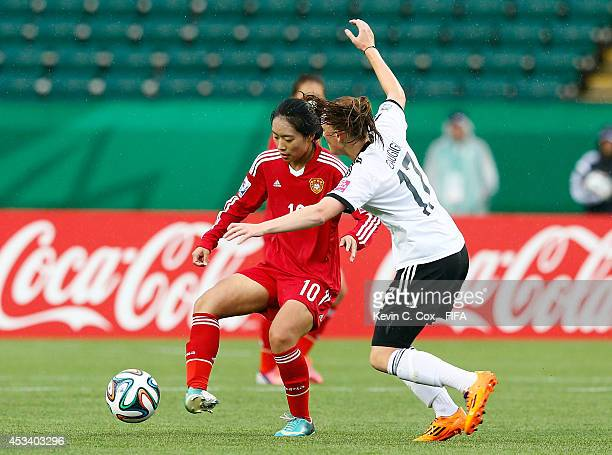 Tang Jiali of China PR in action against Jennifer Gaugigl of Germany during the FIFA U20 Women's World Cup Canada 2014 match between China PR and...