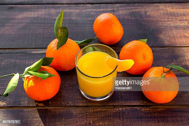 Tangarines, juice in glass on wood