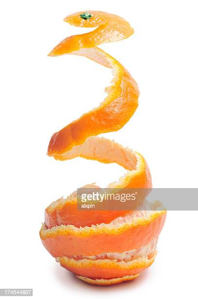 A tangerine with the peel being taken off of in mid air
