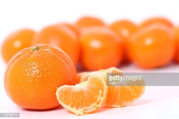 Tangerines and clementine wholes and slices on white