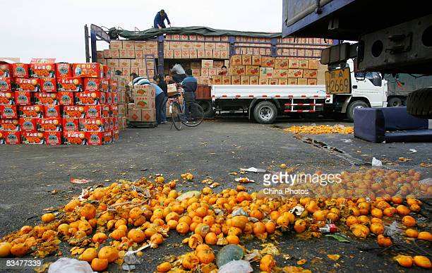 Tangerines are dumped by wholesalers at Beijing's Xinfadi wholesale fruit market where retail customers remain reluctant to buy despite reduced...