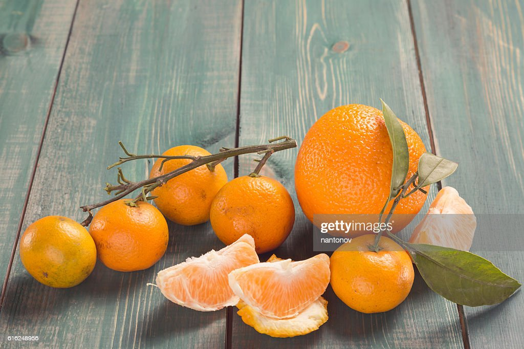 Tangerines with branch, leafs and orange slices on green wooden : Foto de stock