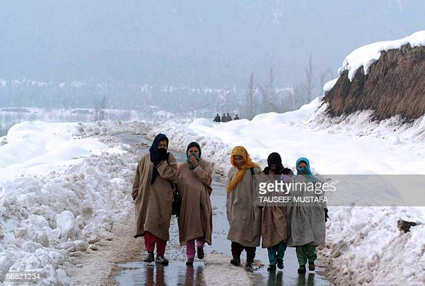 A group of Kashmiri girls walk down a snow covered road near Tangmarg some 40kms north of Srinagar 04 January 2006 Officials say that some 6 to 9...