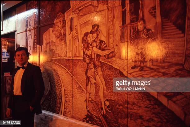 AIRES ARGENTINA Tango Club in San Telmo Quarter the wall's painting represents Tango a couple a paved street the musician playing the bandoneon the...
