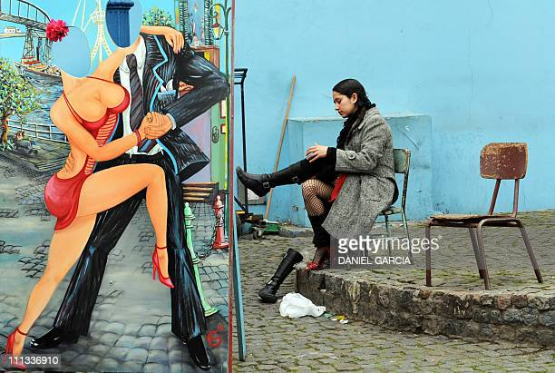 FORUMA tango dancer changes her boots for highheeled shoes before a performance at Caminito Street in Buenos Aires' La Boca neighbourhood on August...
