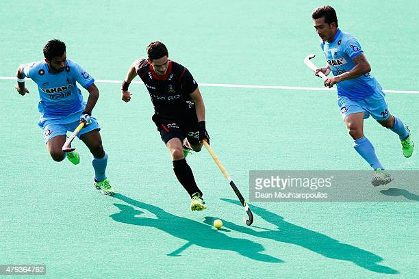 Tanguy Cosyns of Belgium is chased by Chinglensana Kangujam and Manpreet Singh of India during the Fintro Hockey World League SemiFinal match between...