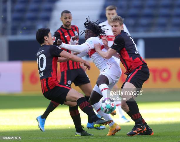 Tanguy Coulibaly of VfB Stuttgart is challenged by Makoto Hasebe of Eintracht Frankfurt and Martin Hinteregger of Eintracht Frankfurt during the...