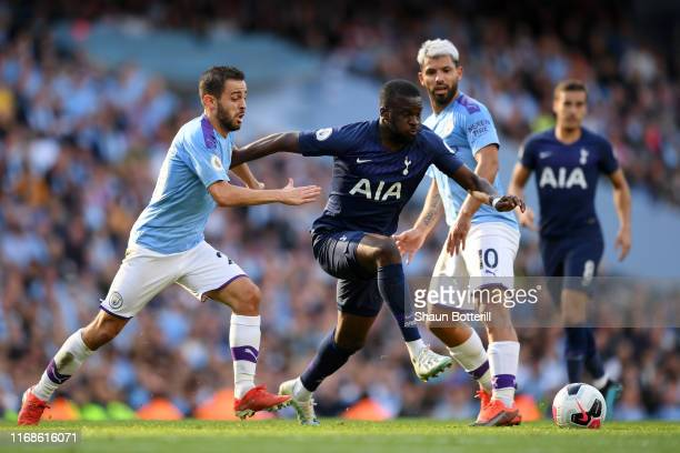 Tanguy Ndombele of Tottenham Hotspur battles for possession with Bernardo Silva of Manchester City as Sergio Aguero of Manchester City looks on...