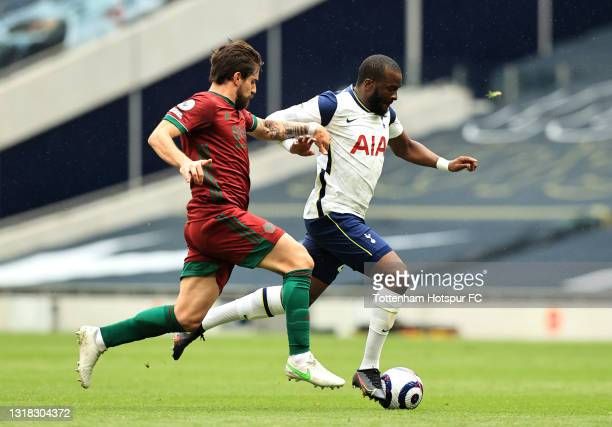 Tanguy Ndombele of Tottenham Hotspur is challenged by Ruben Neves of Wolverhampton Wanderers during the Premier League match between Tottenham...