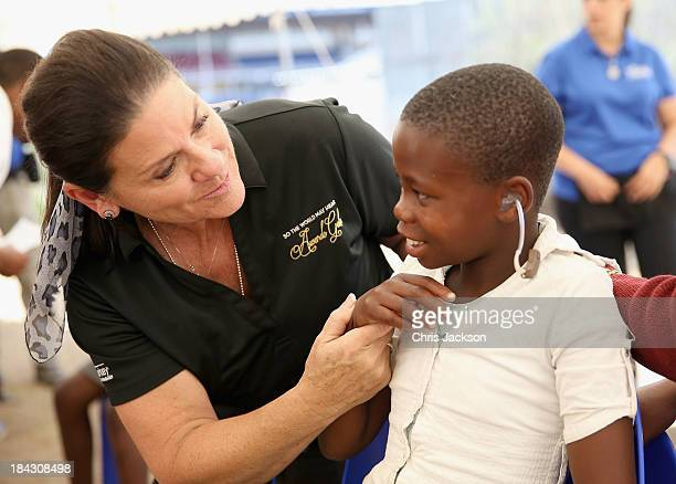 Tani Austin of the Starkey Foundation helps a young child feel the vibration of her voice as she fits a hearing aid at Lesotho Cooperative College on...