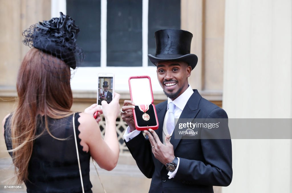 Tania Farah takes a photo of her husband four-time Olympic champion Sir Mo Farah after receiving his knighthood from Queen Elizabeth II at Buckingham Palace on November 14, 2017 in London, United Kingdom.