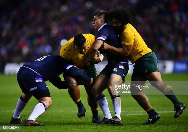 Taniela Tupou of Australia is tackled by Zander Fagerson and Huw Jones of Scotland during the International match between Scotland and Australia at...