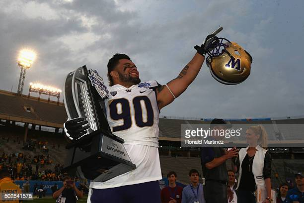 Taniela Tupou of the Washington Huskies holds up the trophy after defeating the Southern Miss Golden Eagles during the Zaxby's Heart of Dallas Bowl...