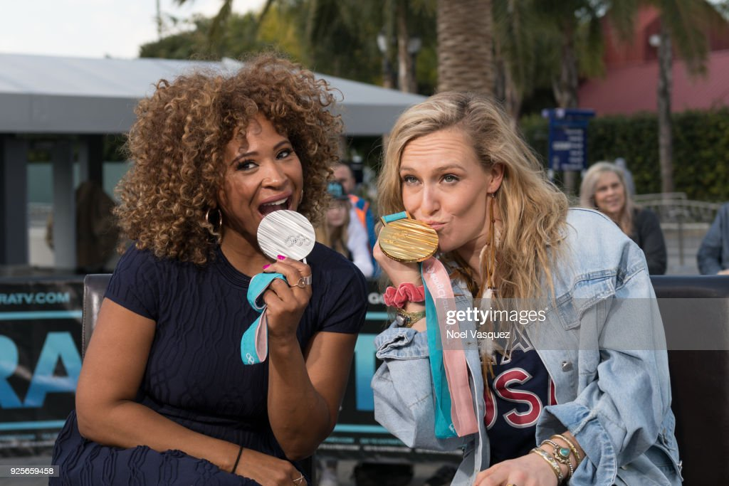 Tanika Ray (L) and Jamie Anderson kiss Olympic medals together at 'Extra' at Universal Studios Hollywood on February 28, 2018 in Universal City, California.