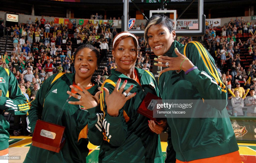 Tanisha Wright #30, Le'coe Willingham #34 and Ashley Robinson #43 of the Seattle Storm show off their 2010 WNBA Championship Rings before the game against the Phoenix Mercury on June 4, 2011 at Key Arena in Seattle, Washington.