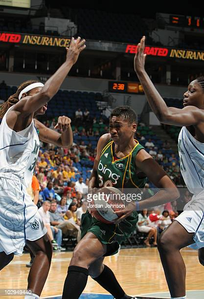 Tanisha Wright of the Seattle Storm looks to shoot under pressure from Rebekkah Brunson and Nicky Anosike of the Minnesota Lynx during the game on...