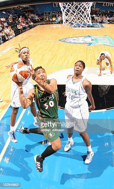 Tanisha Wright of the Seattle Storm shoots under pressure from Rebekkah Brunson and Nicky Anosike of the Minnesota Lynx during the game on July 17...