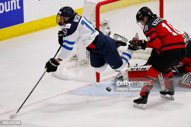 Tanja Niskanen of Finland flies through the air after a shot attempt between Shannon Szabados and Halli Krzyzaniak of Canada in the second period...