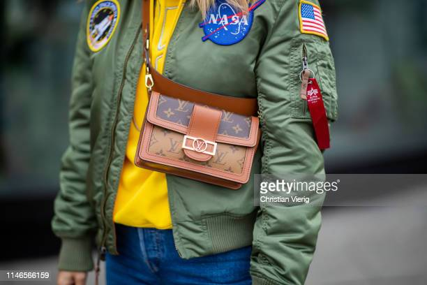 Tanja Trutschnig wearing yellow hoody Louis Vuitton bag olive bomber jacket with Nasa patch cropped denim jeans on May 02 2019 in Berlin Germany