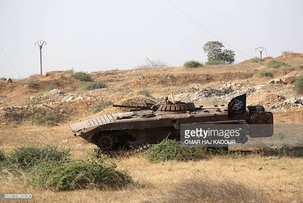 A tank bearing an Islamist flag is seen in a field as a Syrian coalition of jihadists and Islamist rebels seized key positions south of Aleppo in a...