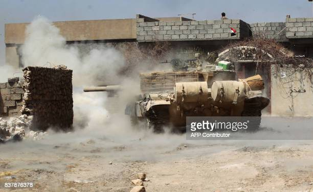 Tank belonging to the Iraqi forces, backed by Shiite fighters from the Popular Mobilization Forces, fires towards jihadist positions as they advance...