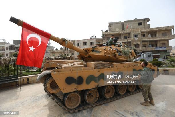 A tank belonging to Turkish soldiers and Ankarabacked Syrian Arab fighters is seen in the Kurdishmajority city of Afrin in northwestern Syria after...
