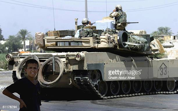 S tank blocks a street in Sadr City where US troops were trying to defuse land mines laid by Mahdi army militia men on August 16 2004 in Baghdad Iraq...