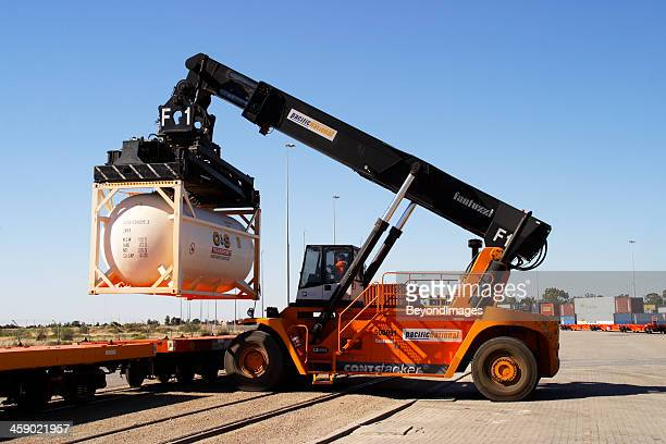 tank container transfer from train to truck - shunting yard stock photos and pictures