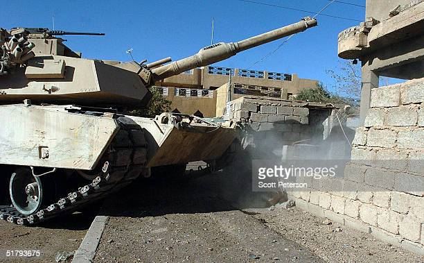 A tank crushes a wall to permit side entry as US Marines of the 1st Light Armored Reconnaissance company as part of 1st Battalion 3rd Marines clear...
