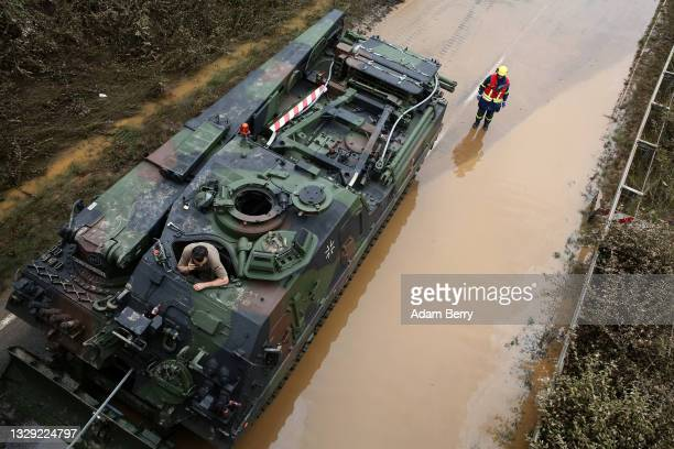 Tank driver speaks on a mobile phone as he waits for rescue workers to prepare abandoned vehicles for him to pull from flooded highway 265 after a...