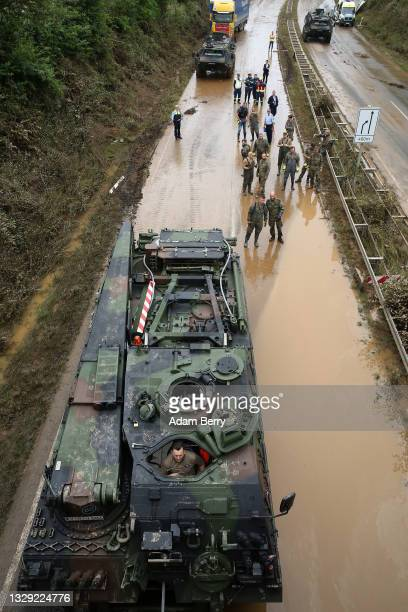 Tank driver waits for rescue workers to prepare abandoned vehicles for him to pull from flooded highway 265 after a landslide caused by a major flood...