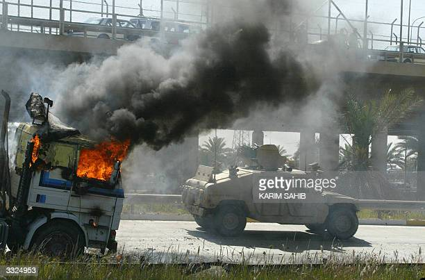 US tank drives past a burning truck attacked by insurgents on the road leading to Baghdad's International Airport 10 April 2004 in Baghdad The truck...