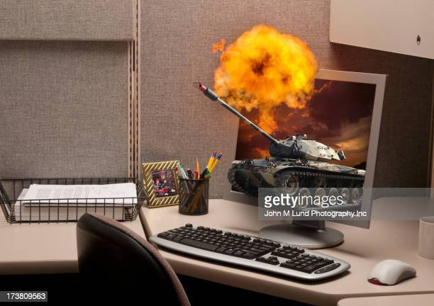 Tank emerging from computer screen in cubicle