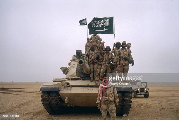 A tank flying the Saudi Arabian flag travels with American soldiers in an allied convoy heading north through Saudi Arabia during the Persian Gulf War