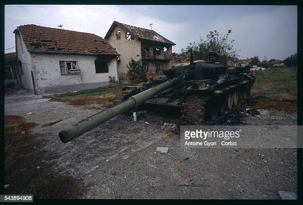 A tank from the Yugoslavian federal army remains in front of crumbled houses after fights with Croatian militias around Vukovar