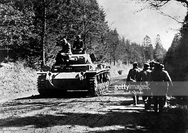 A tank going along a road in the Ardennes Forest meeting a sappers patrol coming back from a mission during the World War II Ardennes 14th May 1940