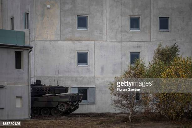 A tank 'Leopard' is placed between two buildings on October 26 2017 in Schnoeggersburg Germany The urban agglomeration called 'Schnoeggersburg' is...