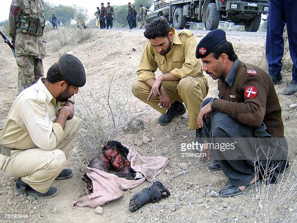 Pakistani security officials look at the remains of a suspects suicide bomber in the town of Tank some 60 Kms west of Dera Ismail Khan 03 January...