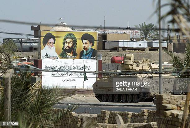 US tank rolls past a picture of leading Shiite Muslim figures from L to R Mohammed Sadeq alSadr Imam Ali and Mohammed Baqr alSadr in Baghdad's...