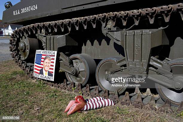 A tank with a mock display of a crushed Hillary Clinton rag doll in prison stripes decorates the front lawn of a gun store in Schuylkill County...
