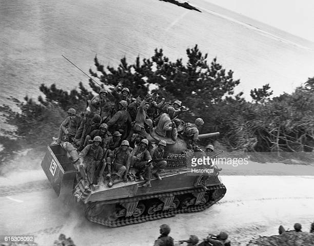 Tank-borne infantry moving up to take the town of Ghuta before the Japanese can occupy it. The men are members of the 29th Marines. Okinawa, April 1,...
