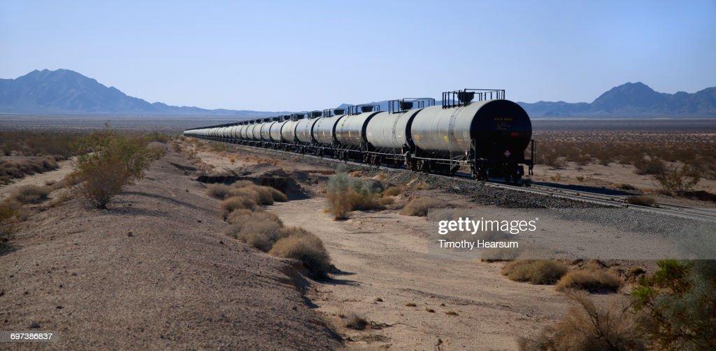 Tanker cars on railroad tracks; mountains beyond : Stock Photo