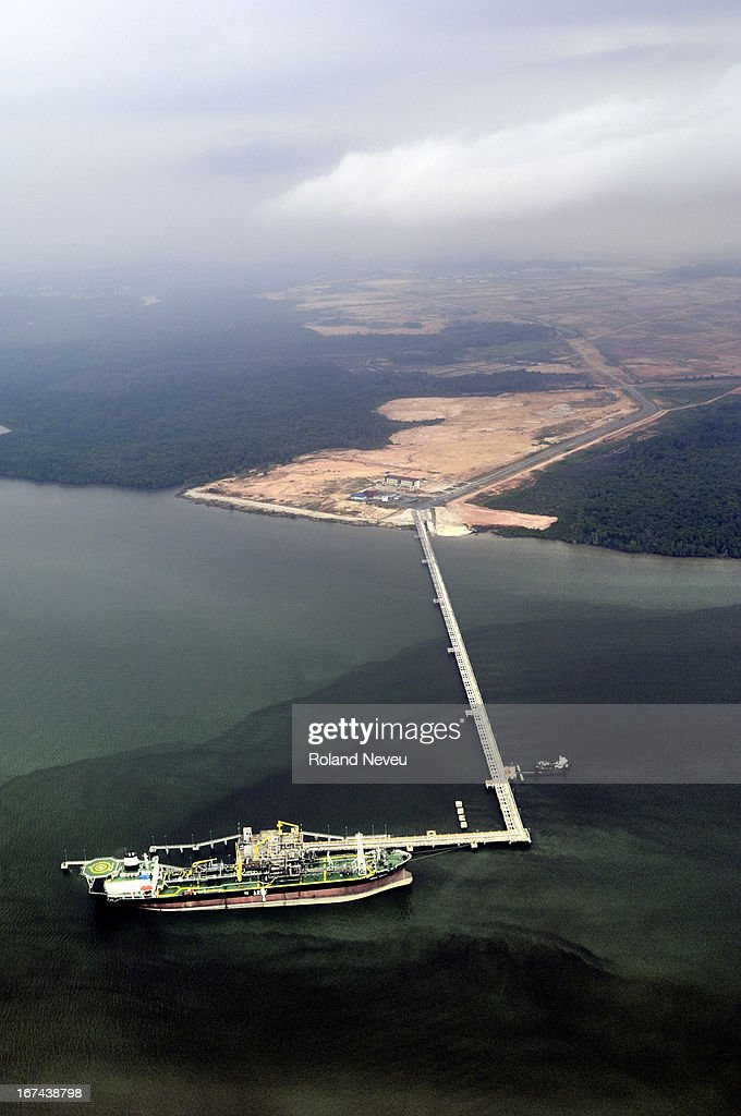A tanker docked at an oil terminal in the vicinity of the Changi airport with an obvious oil slick surrounding it. Seen from a landing airliner..