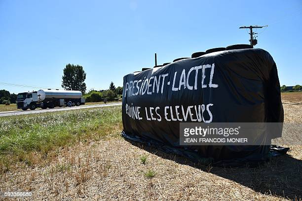 A tanker drives past a block made of straw bales on which is written 'President Lactel ruin breeders' in Allonnes near Le Mans northwestern France on...
