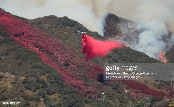 A tanker drops fire retardant on the hillside along Cajon Road on as firefighters build a line to stop the Blue Cut Fire onThursday ///ADDITIONAL...