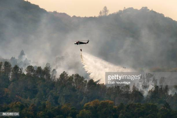 A tanker helicopter drops water on a wildfire on October 16 2017 in Oakville California At least 40 people were killed with many are still missing...