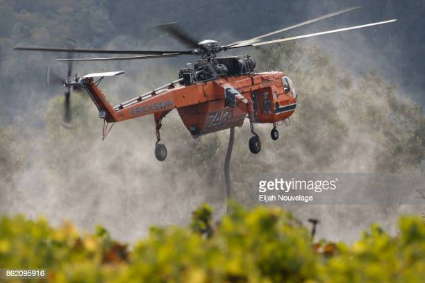 A tanker helicopter lifts off after refilling with water while fighting a wildfire on October 16 2017 in Oakville California At least 40 people were...