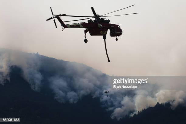 Tanker helicopters fight a wildfire on October 16 2017 in Oakville California At least 40 people were killed with many are still missing and at least...
